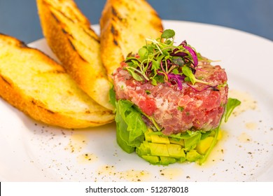 Ahi tuna tartare stacked with avocado, arugula, topped with micro greens, served with grilled crostini bread