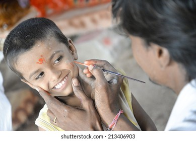 AHMEDABAD, GUJARAT - 24th  SUNDAY AUGUST 2014 :Boy getting paint from his dad, while dad working on idols. Gulbai tekra is the single largest supplier of Ganesha idols in Ahmedabad, Gujarat India.