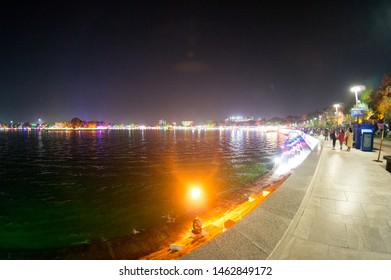 Ahmedabad, Gujarat, India - circa 2018 : People sitting on the circular area around kankaria lake in Ahmedabad. The beautiful colorful night lights and huge expanse make this a very popular spot for