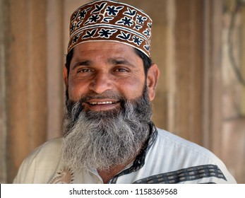 AHMEDABAD, GUJARAT / INDIA - FEB 17, 2017: Middle-aged Indian Muslim man with Muslim-style trimmed full beard wears a patterned Oman cap and smiles for the camera, on Feb 17, 2017.
