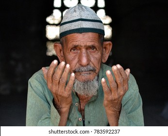 AHMEDABAD, GUJARAT, INDIA - FEB 19, 2017: Old Indian Muslim man with lived-in face,  wearing an Islamic prayer cap (taqiyah), prays with both hands at Hazmat Hair Ra Masjid (Asarwa), on Feb 19, 2017.