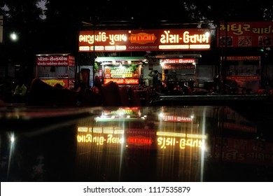 AHMEDABAD, GUJARAT, INDIA, JUNE 07, 2018: Manek Chowk Khau Gali, a street of popular outdoor eateries at night. Reflection of the name board on steel dining table.