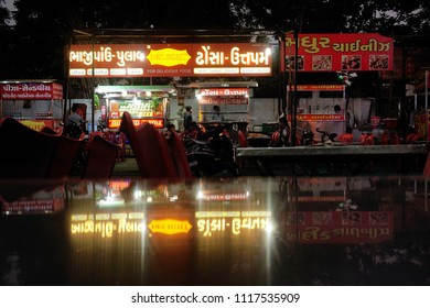 AHMEDABAD, GUJARAT, INDIA, JUNE 07, 2018: Manek Chowk Khau Gali, a street of popular outdoor eateries. Reflection of the name board on a shiny steel-top dining table.
