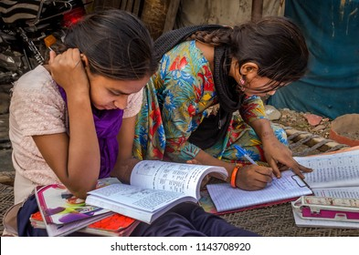 AHMEDABAD, INDIA - DECEMBER 10, 2017: Unidentified school girls of Indian Ethnicity sitting on cot doing homework with books and exercise notebooks.