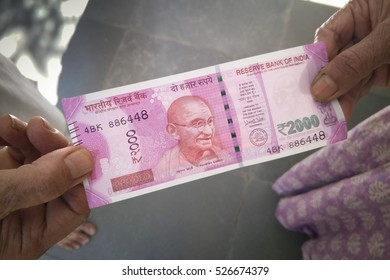 Ahmedabad, India - November 26, 2016: Customer is paying with new 2000 Rupee Indian currency. India demonetized 500 and 1000 rupee currency notes on November 8th to curb black money problem