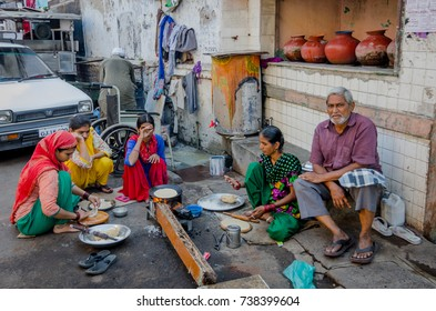 AHMEDABAD, INDIA - NOVEMBER 27, 2016: Muslim women cooking chapatti and food for family on the side of the street in heritage city Ahmedabad, Gujarat, India