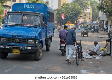 AHMEDABAD, INDIA - OCTOBER 30, 2016: Police stopped to purchase an item from an unidentified newspaper seller with a pitch on a busy city street in the early morning