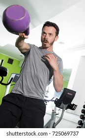 Ahtletic man working out using a purple kettlebell in gym