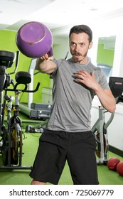 Ahtletic man working out using a purple kettlebell
