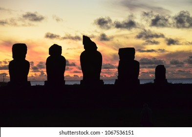 Ahu Tahai Silhouettes with Funny-Looking Middleman at Sunset with Dark Clouds over Hanga Roa Harbour, Rapa Nui (Easter Island)