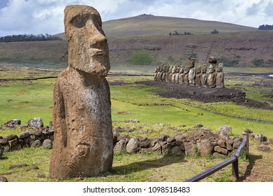 """Ahu Tongariki with volcano Poike in the background and the nearby """"Traveling Moai"""" in the foreground.Rapa Nui National Park,  Easter Island, Chile.  UNESCO World Heritage Site"""