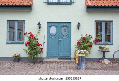 AHUS, SOUTH SWEDEN - JUNE 28, 2014: Pretty home entrance with green washed wall, turquoise door and roses on a cobble stone street on June 28, 2014 in Ahus, South Sweden.