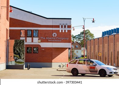 Ahus, Sweden - March 20, 2016: Architectural detail of the Absolut Company factory, the place where Absolut Vodka is made. Red bricks with white details logo visible. Securitas car outside.