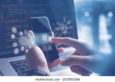 AI, Artificial Intelligence, Big data, Internet of Things IoT. Man, programmer, software engineer using mobile smartphone by id touch on screen, coding on laptop computer with technology background