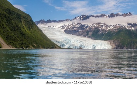 Aialik Glacier in Kenai Fjords National Park, Alaska, USA. Glacier as seen from kayaks in the water. Abundant blue ice visible on glacier.