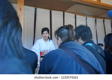 AICHI, JAPAN - January 2, 2018: People flocking to Atsuta Shrine for the first shrine visit of the year (Hatsumoude) and buying fortune-telling paper strips (Omikuji) from the shrine maidens (Miko).