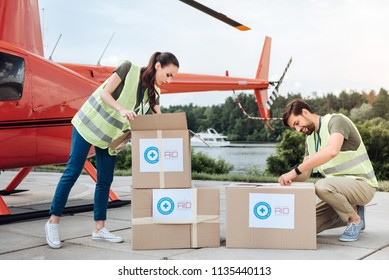 Aid in box. Concentrated two volunteers posing near helicopter and examining boxes