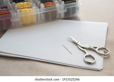 Aida white canvas, needle, needlework scissors and a box with multicolored embroidery threads, needlework and cross stitch concept