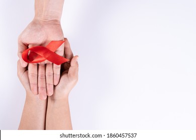 Aids awareness, man and woman hands holding red ribbon on white background with copy space for text. World Aids Day, Healthcare and medical concept.