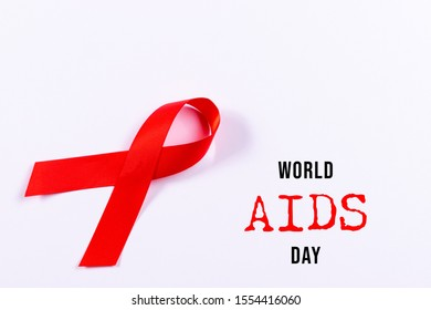 AIDS awareness red ribbon on white background.  World AIDS Day. Copy space.