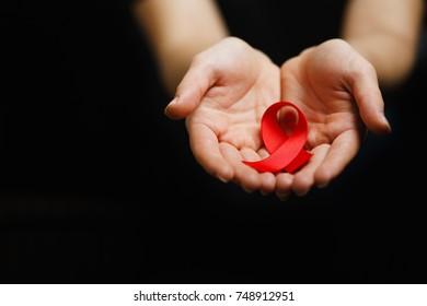 Aids ribbon on hands, hiv, red ribbon symbol of struggle,  on dark background