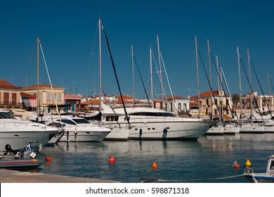 AIGINA, GREECE - APRIL 21, 2011: Aigina island port, traditional fishing boats docked, Isodia Theotokou church, Saronic gulf, Greece