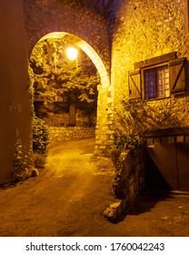 Aiguines, France - July 8, 2011: Night view empty town street with lantern and interesting window, stone building.