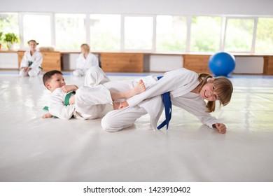 Aikido fight. Boy and girl wearing white kimono having aikido fight in sport school