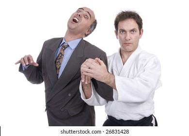 aikido man hurting a successful businessman (isolated on white)