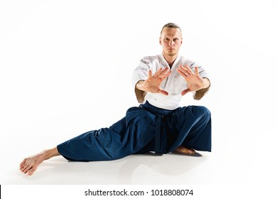 Aikido master practices defense posture. Healthy lifestyle and sports concept. Man with beard in white kimono on white background. Karate man with concentrated face in uniform.