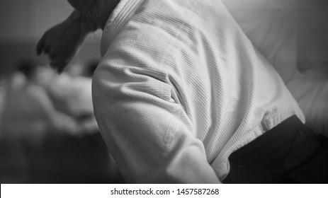 Aikido training. Black and white image. Traditional form of clothing in Aikido. Background image. No faces and recognizable elements!