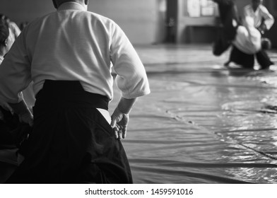 Aikido training. Black and white image. The teacher shows reception.  Traditional form of clothing in Aikido.