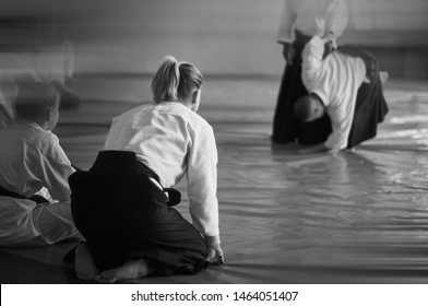 Aikido training. Black and white image. The teacher shows reception.  Traditional form of clothing in Aikido. Background image. Photo from the back. No faces and recognizable elements!
