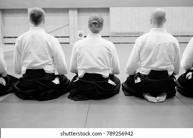 Aikido training participants sit on a mat in special clothing of hakama aikido