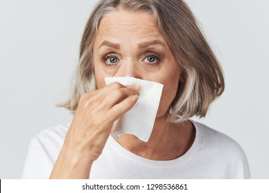 Ailing elderly woman wipes her nose with a handkerchief