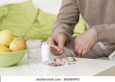 Ailing old man taking pills with water
