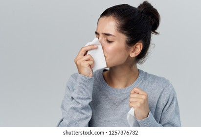 Ailing woman wipes her nose with a handkerchief