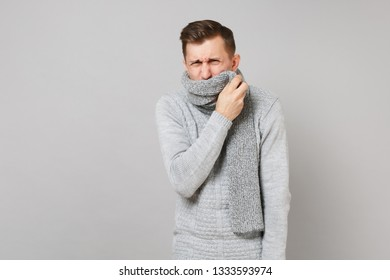 Ailing young man in gray sweater covering mouth with scarf sneezing or coughing isolated on grey wall background. Healthy lifestyle, ill sick disease treatment cold season concept. Mock up copy space