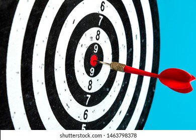 Aim with arrow in the center. Target on a blue background with a red dart.