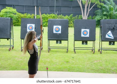 aiming archers,Female ginger hair archer shooting targets with her bow and arrow