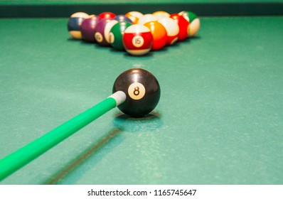Aiming billiard stick on colorful billiard balls and start the game