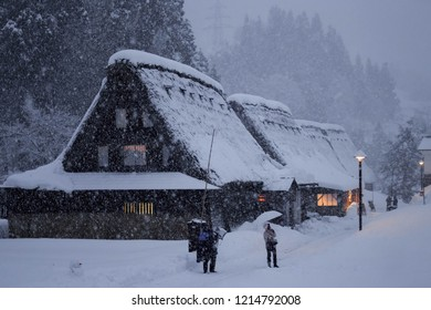 Ainokura, Japan - December 30, 2017: Tourist uses umbrella to shelter from heavy snow in small Japanese mountain village and tourist attraction due to its traditional thatched roof buildings
