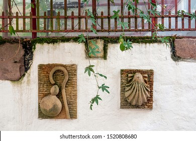 AINT-JEAN-PIED-DE-PORT, FRANCE - AUGUST 20, 2019. The town is on 3 paths of pilgrimage to Santiago de Compostela. On a wall of a house, two symbols of St Jacques de Compostela.
