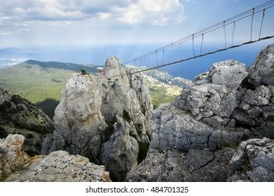 Ai-Petri, Crimea, Russia - August 11, 2016: Hanging bridge in steep rocks with walking man.