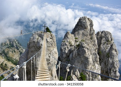 Ai-Petri, Crimea, Russia - August 14, 2015: Hanging bridge in steep rocks with going man and woman.