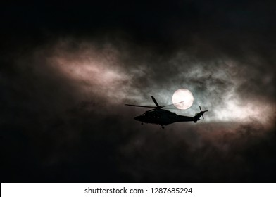 An air ambulance helicopter departing Gosford Hospital flying through nimbostratus storm cloud at sunset. In silhouette with a slight tinge pink cloud in a dark sky. New South Wales, Australia.