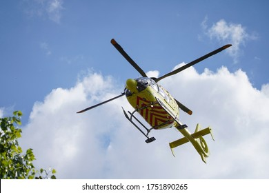 The air ambulance, service arrives at the scene of an accident. Flying yellow medical ambulance helicopter over the trees. Background of blue sky with clouds. Pest county / Hungary - 06/01/2020