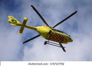 The air ambulance, service rush to the scene of an accident. Flying yellow medical ambulance helicopter. Background of blue sky with clouds. Pest county / Hungary - 06/01/2020