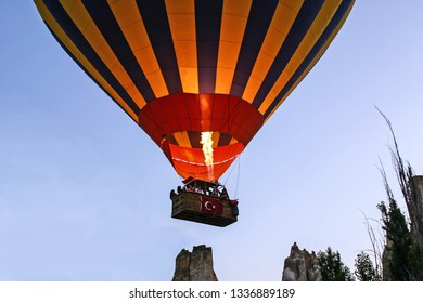 An Air Balloon with its basket adorned by the Turkish Flag lifts off in the early morning to soar over the famous volcanic outcroppings of Cappadocia