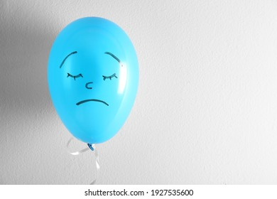 Air balloon with drawn sad face on white background. Space for text